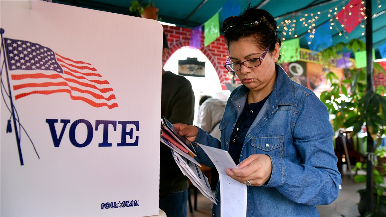 Une femme tient son bulletin de vote à la main à côté de l'isoloir.