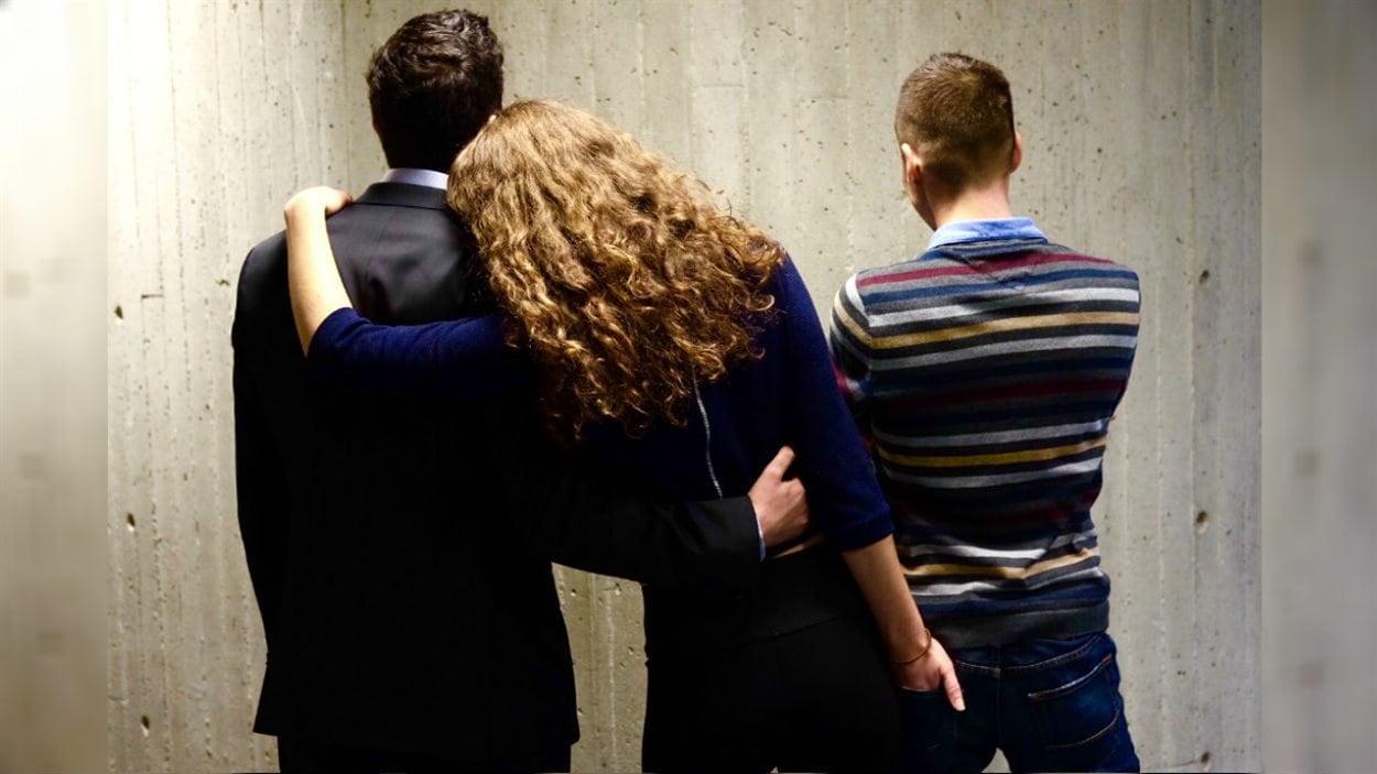 Une femme polyamoureuse enlace deux hommes