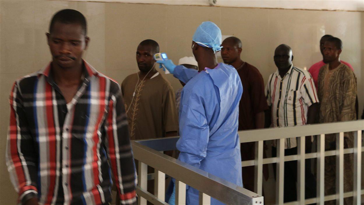 Un travailleur de la santé prend la température de personnes en Guinée, le 18 mars 2016, pour s'assurer qu'ils ne soient pas infectés par le virus Ebola