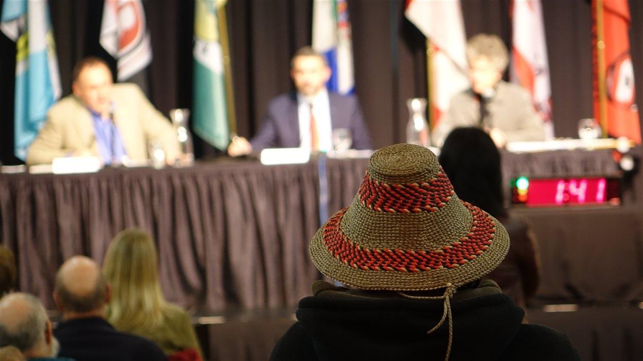 un homme avec un chapeau traditionnel attend de poser une question lors d'un débat