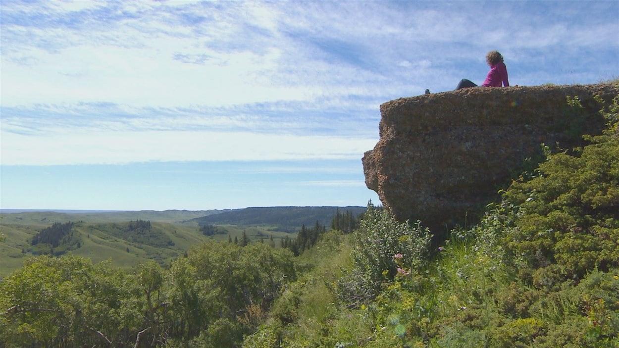L'hydrologue Nathalie Brunet regarde le paysage vallonneux du sud-ouest de la Saskatchewan, assise sur la falaise de conglomérat des Cypress Hills.