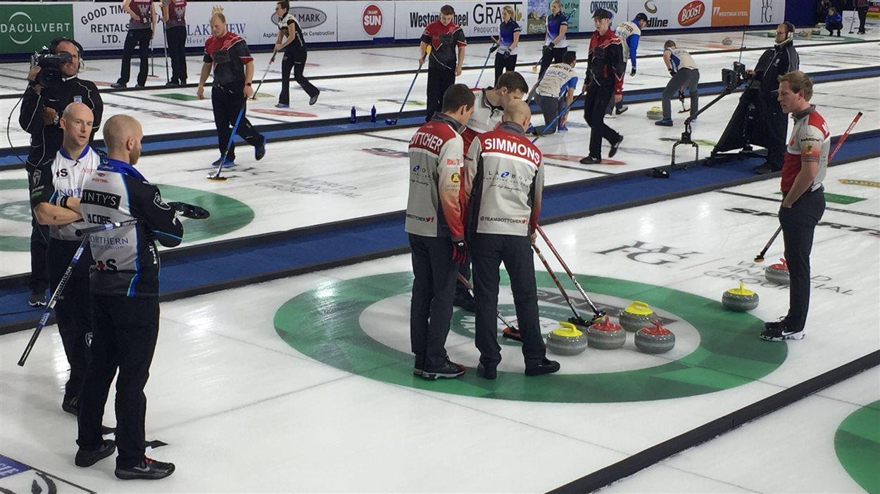 Les membres de l'équipe de Brendan Bottcher discutent de stratégie lors d'un match du Tournoi des maîtres de curling à Okotoks