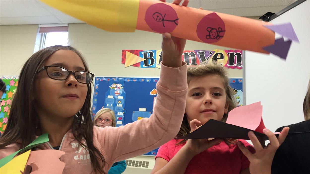 Des élèves de l'École publique Foyer-Jeunesse montre leurs bricolages, une fusée et une maison pour Capot l'ourson!