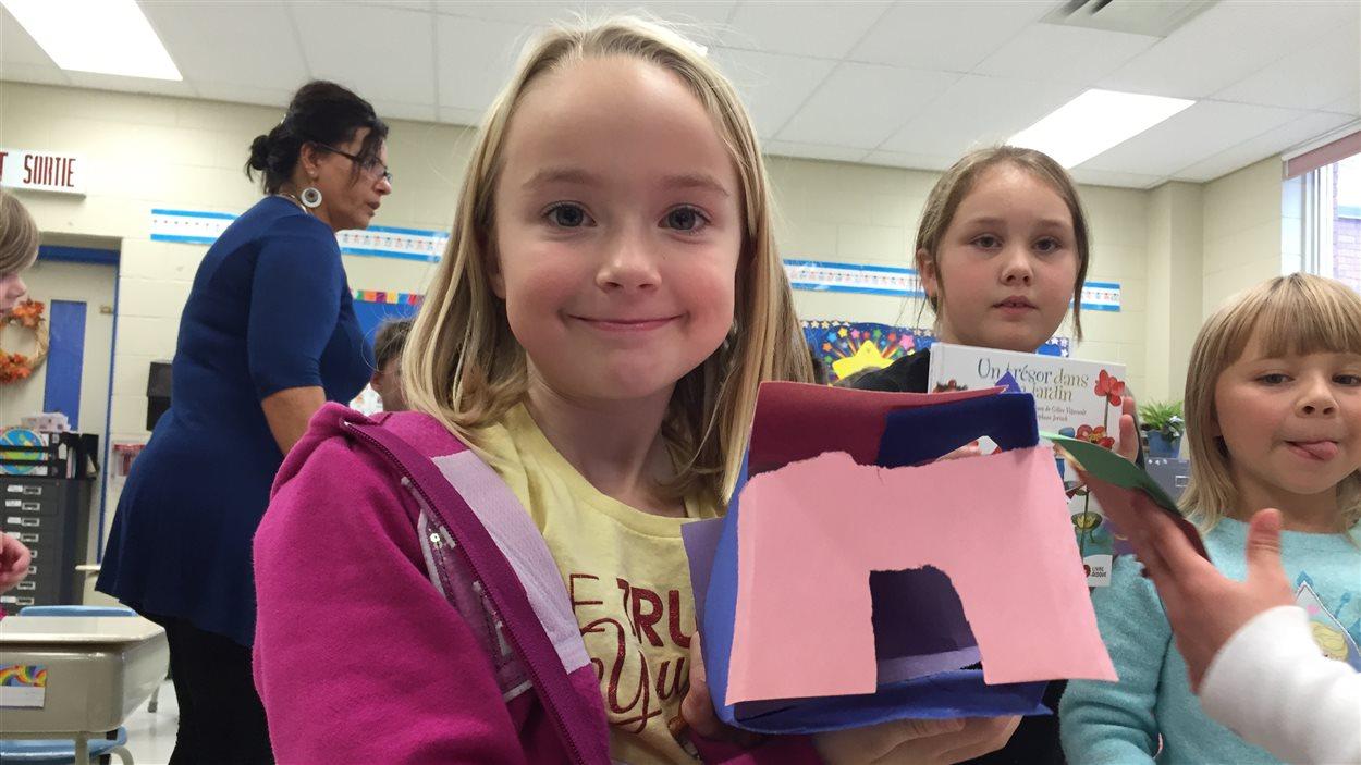 Une élève de l'École publique Foyer-Jeunesse montre son bricolage, une maison pour Capot l'ourson!