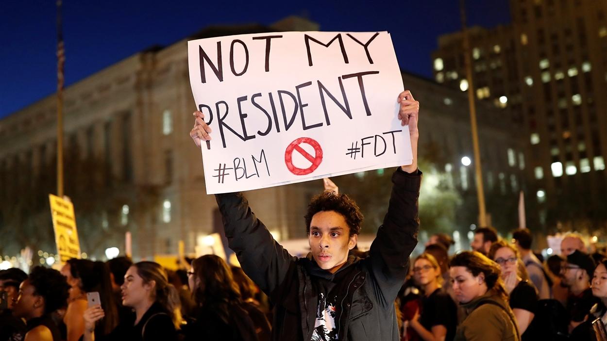 Un manifestant tient une pancarte où l'on peut lire