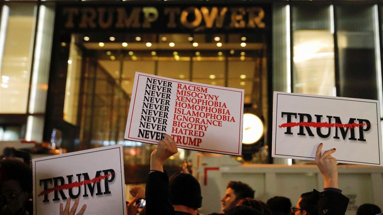 Des gens tiennent des pancartes à bout de bras devant la Trump Tower, dans Manhattan, à New York.