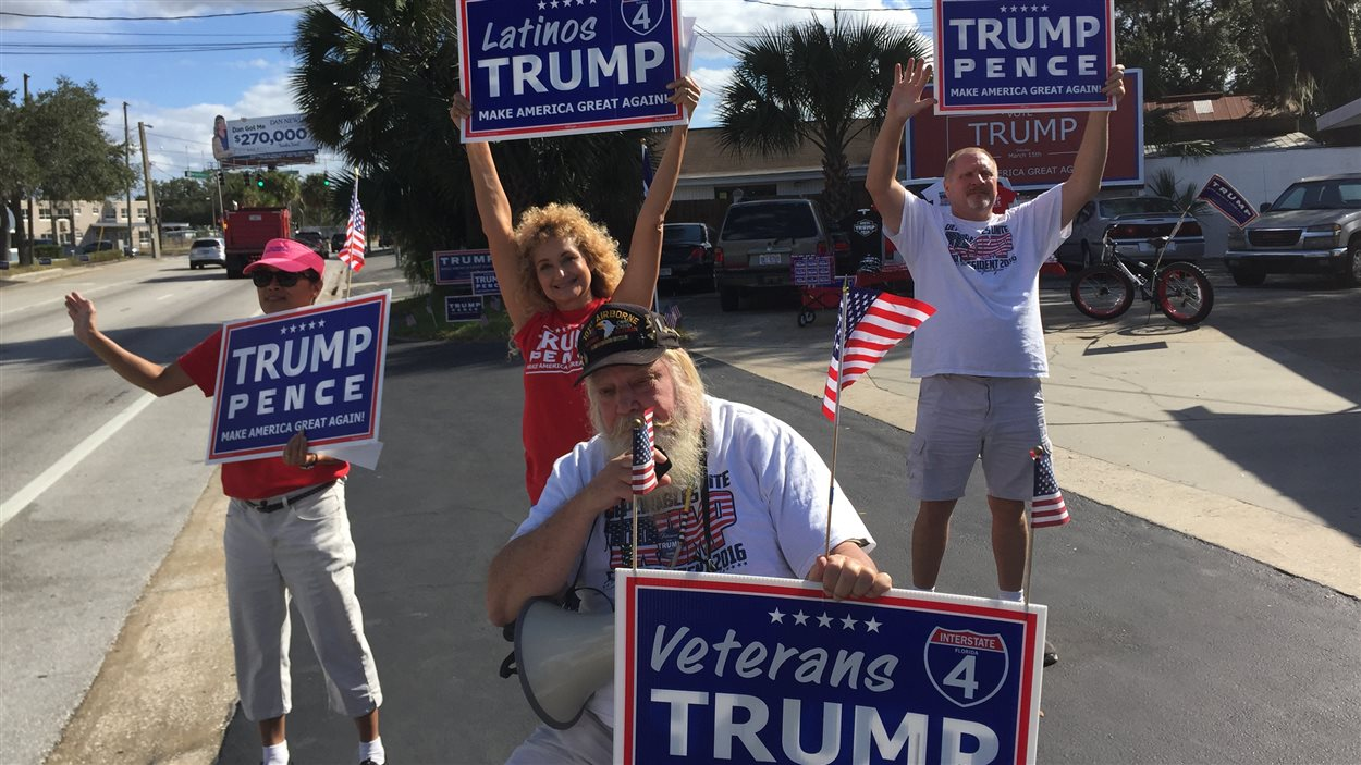 Des partisans de Donald Trump tiennent des pancartes sur le trottoir