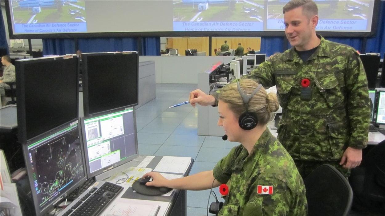 Une militaire observe son écran d'ordinateur.