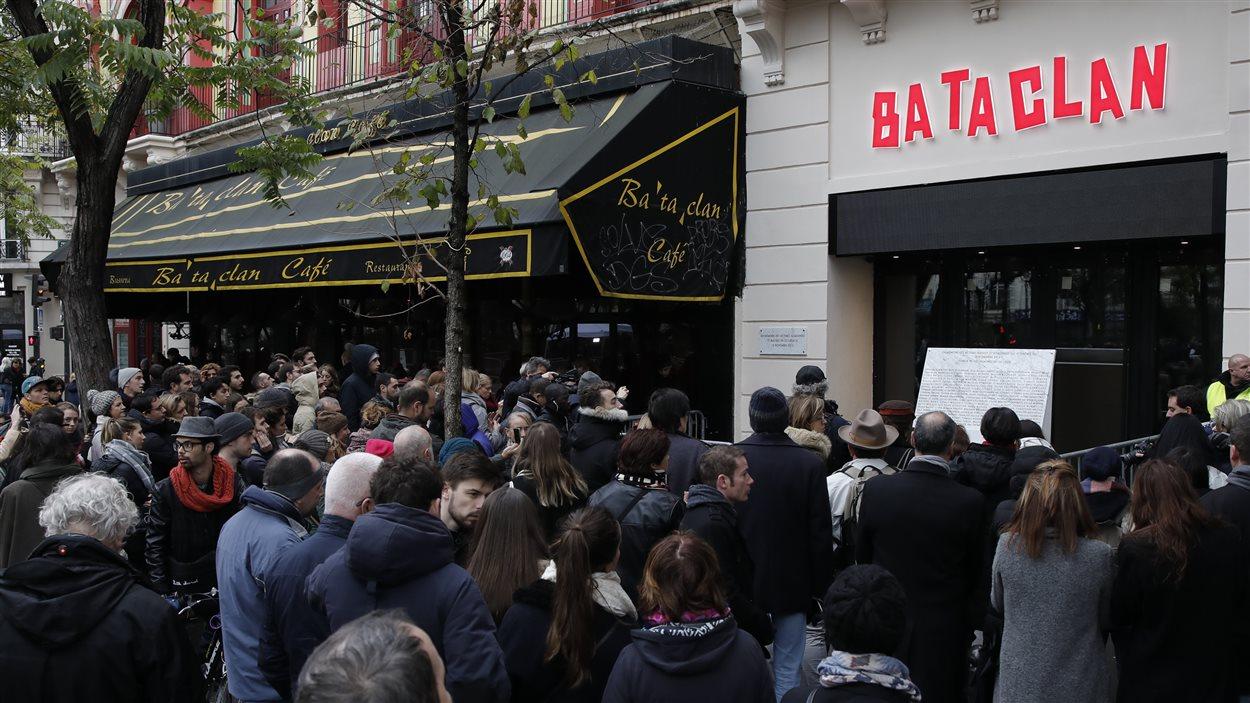 Des gens se rassemblent devant une plaque commémorative dévoilée par le président français François Hollande et la mairesse de Paris Anne Hidalgo devant la salle de concert du Bataclan, à Paris, en France, le 13 novembre 2016, après une cérémonie organisée pour les victimes des attentats de Paris.