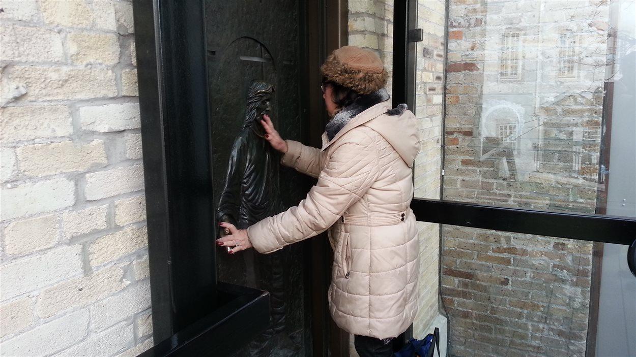 Une pèlerine devant la porte sainte de la basilique-cathédrale Notre-Dame de Québec