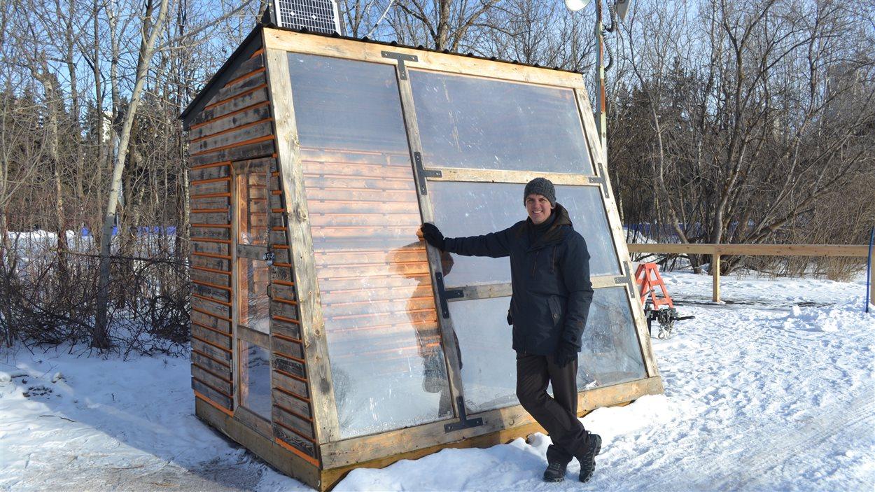 Daniel Cournoyer devant une cabine en bois dans un parc.