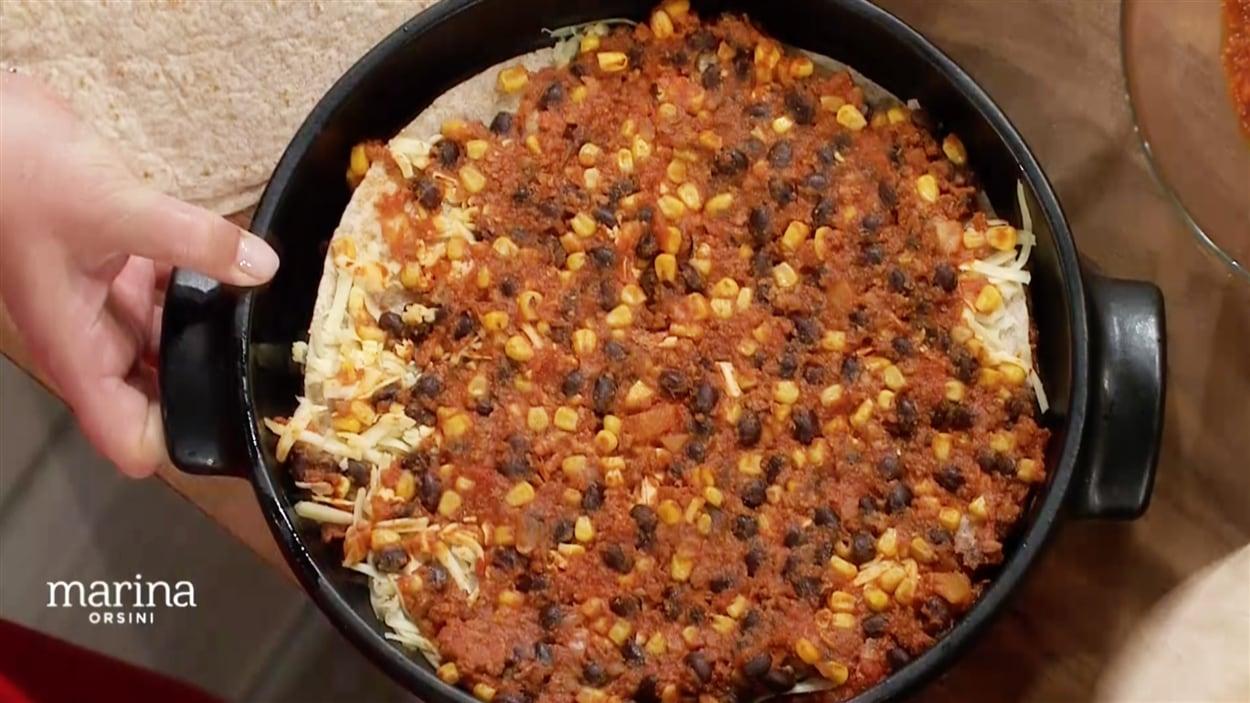 Une tortilla recouverte de fromage, de haricots rouges, de tomates et de maïs