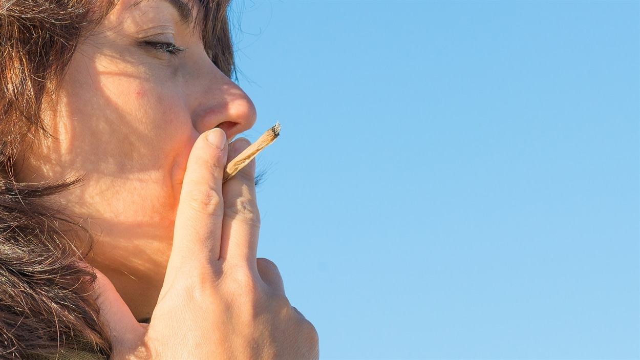 Une femme fume un joint.