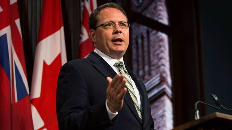 Mike Schreiner se tient devant des drapeaux de l'Ontario