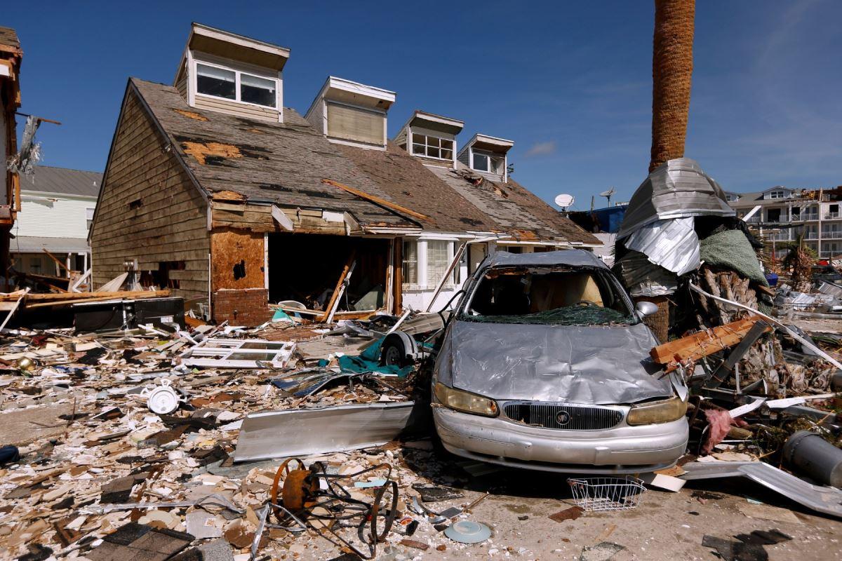 Une maison à moitié détruite, une voiture bosselée et un terrain résidentiel recouvert de détritus.