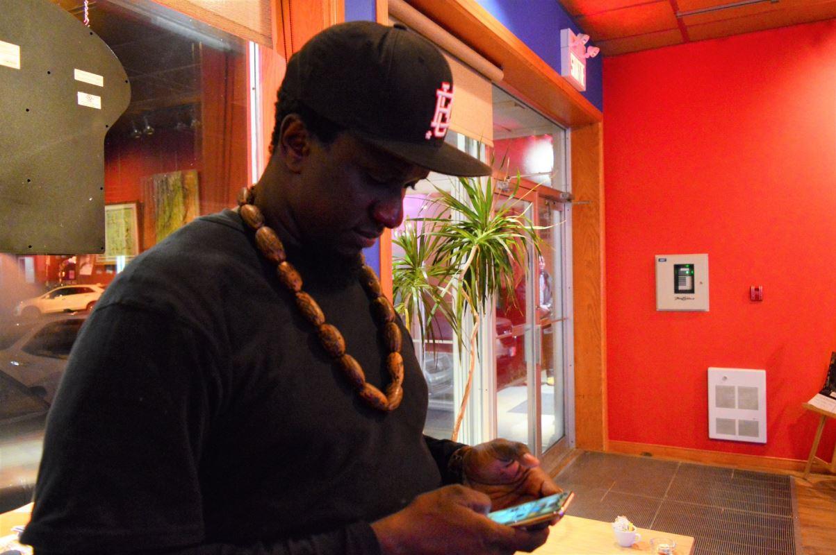 un homme avec une casquette lisant sur son cellulaire.