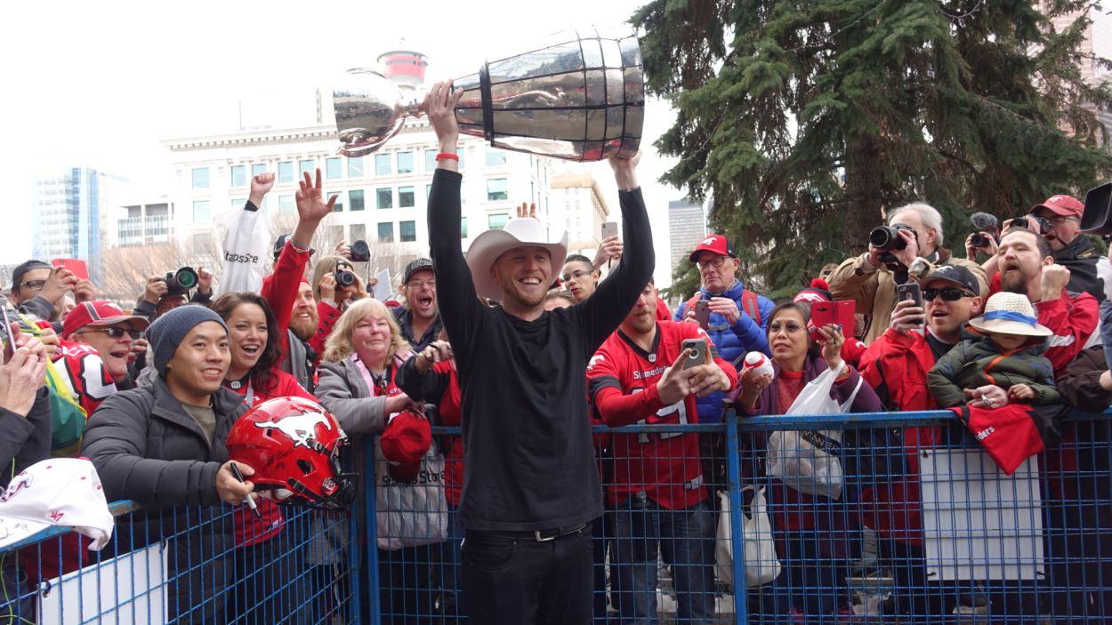 Un homme coiffé d'un chapeau de cowbow brandit un trophée à bout de bras.