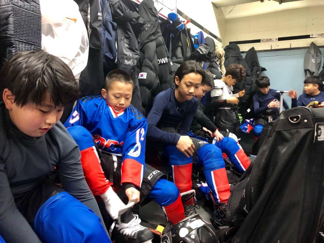 Les jeunes hockeyeurs de la Corée du Sud en train de s'habiller dans la chambre des joueurs en vue de leur premier match du tournoi auquel ils participent.