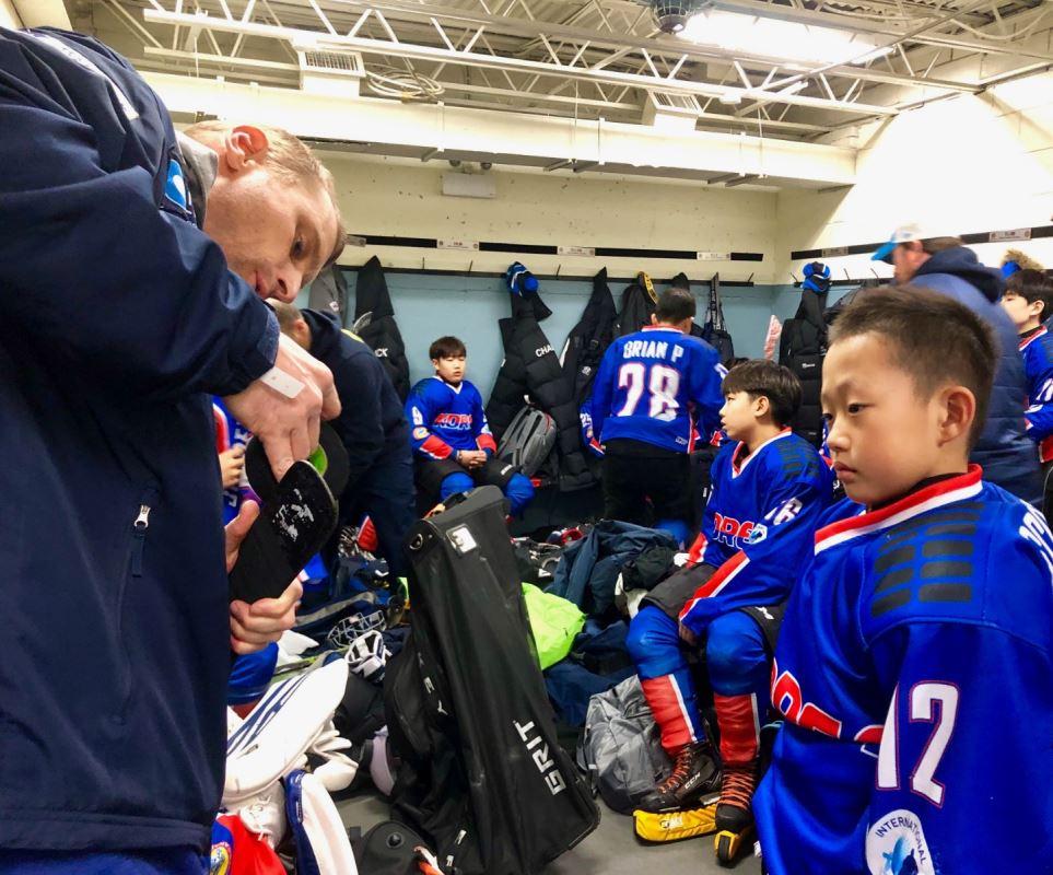 Un joueur de hockey regarde son entraîneur préparer son équipement pour son match.