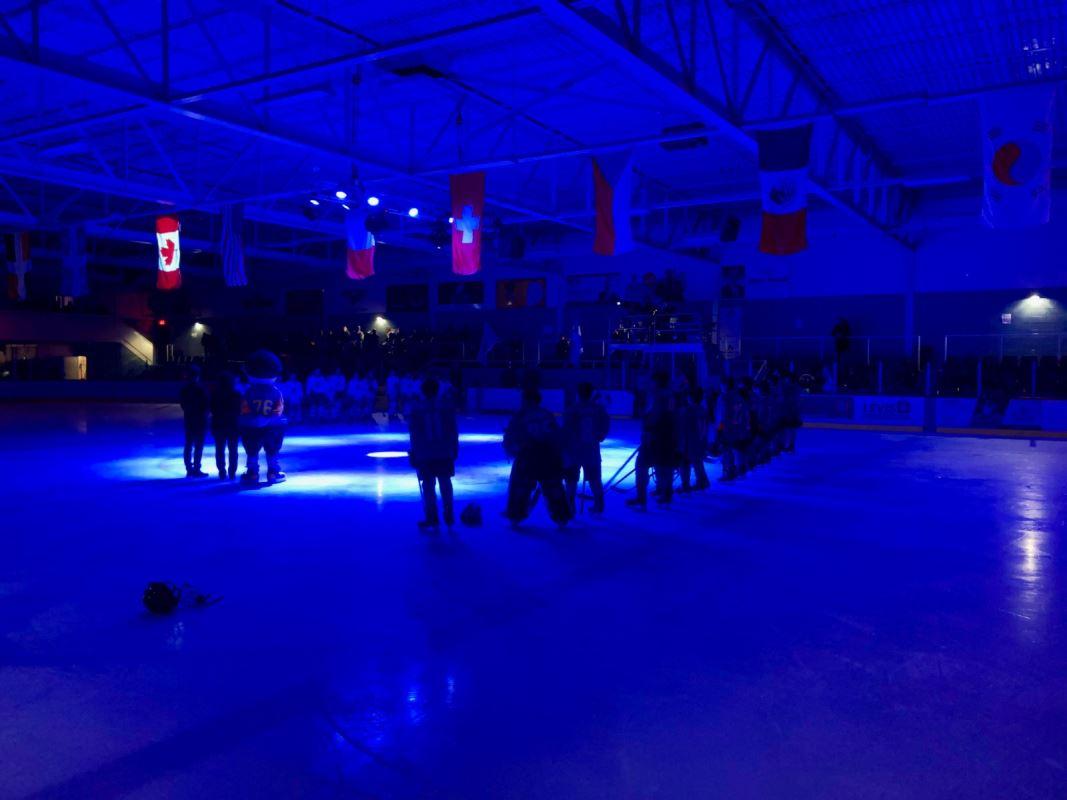 Deux équipes de jeunes hockeyeurs face à face sur la glace dans un aréna pour la présentation de l'hymne national avant le match.