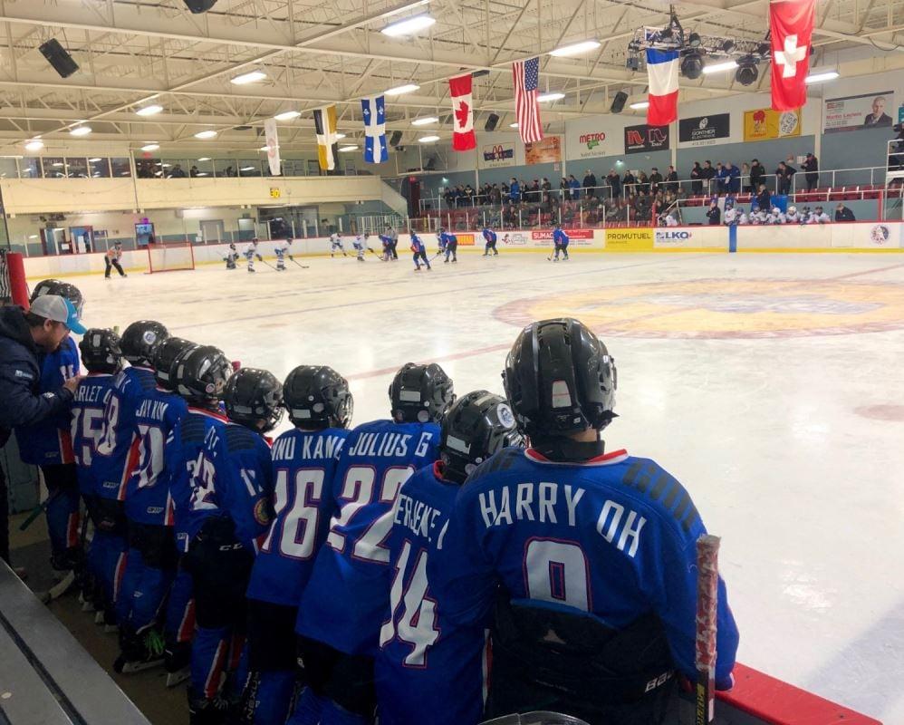 Des jeunes hockeyeurs de la Corée du Sud sur le banc des joueurs pendant leur partie de hockey dans un aréna.