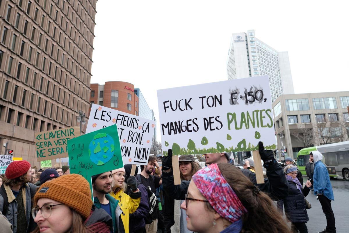 Des manifestants tenant des pancartes. Sur la première, il est inscrit « Il n'y a pas de planète B » et sur la deuxième il est inscrit « Fuck ton F-150, mange des plantes ».