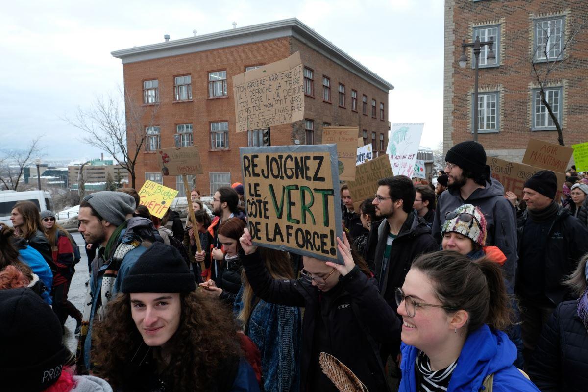 Des manifestants tenant des pancartes, sur la première il est inscrit « Ton arrière-arrière grand-père il a défriché la Terre, ton père il l'a détruite et pis toé mon p'tit gars qu'est-ce tu vas fairte avec ce mess-là » et sur la deuxième il est inscrit « Rejoignez le côté vert de la force »