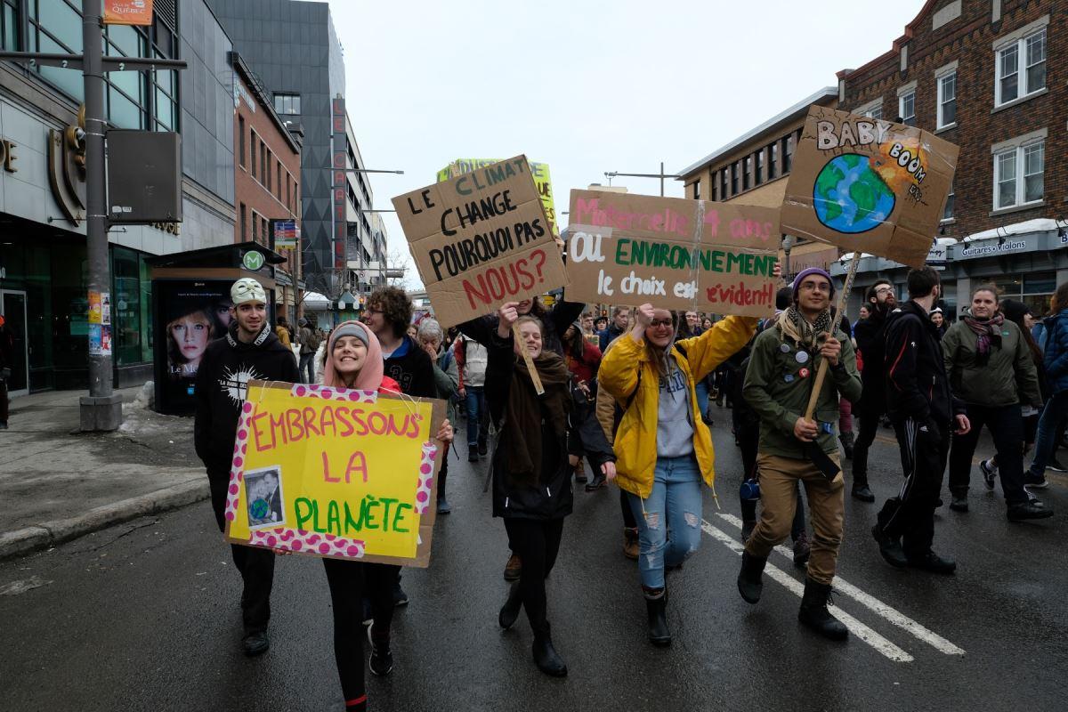 Des manifestants tenant quatre pancartes. Sur la première il est inscrit « Embrassons la planète », sur la deuxième il est inscrit « Le climat change pourquoi pas nous? », sur la troisième il est inscrit « Maternelle 4 ans ou environnement le choix est évident » et sur la quatrième il est inscrit « Baby boom » avec un dessin de planète qui explose.