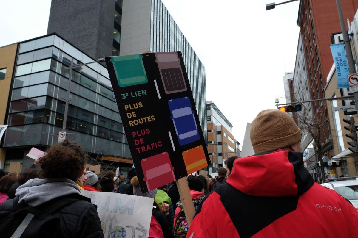 Une pancarte sur laquelle il est inscrit « Troisième lien, plus de route, plus de trafic »