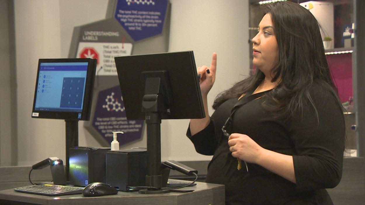 Une jeune femme manipule un ordinateur tactile dans le magasin.