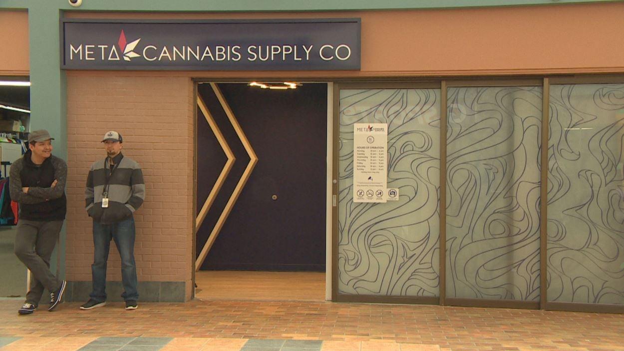 Vue de la façade du magasin Meta Cannabis d'Opaskwayak, avec une vitrine neutre. Deux employés sont à l'entrée pour accueillir les clients et vérifier qu'ils ont l'âge légal pour rentrer.