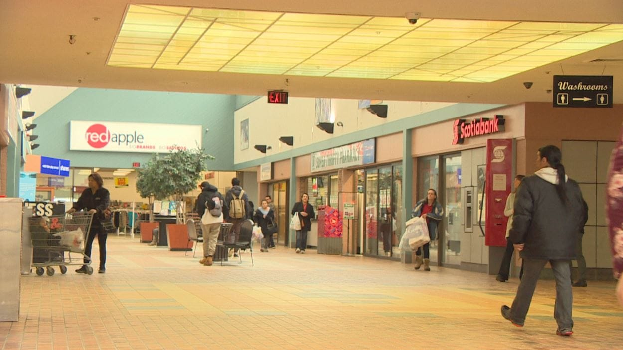Intérieur d'un centre commercial : on voit plusieurs magasins et des clients qui marchent dans le couloir.