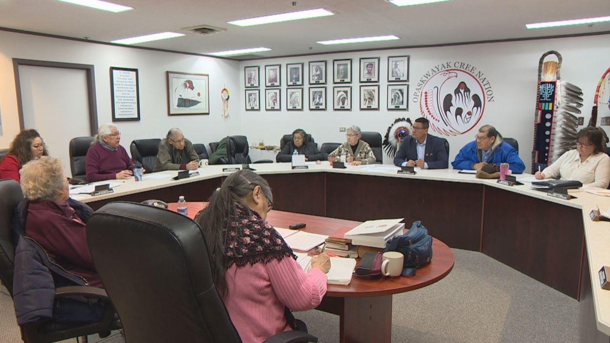 Des conseillers et personnes âgées assis autour d'une grande table circulaire, dans une salle de conseil.