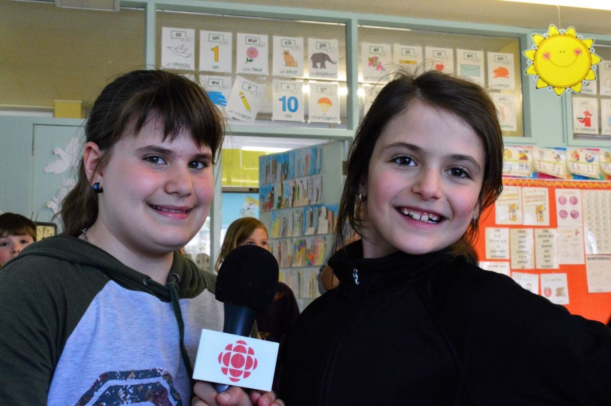 deux jeunes filles posent avec un micro Radio-Canada