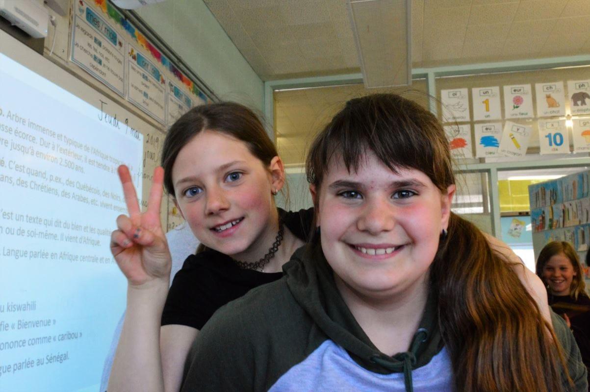 deux jeunes filles souriante dont l'une est sur le dos de l'autre