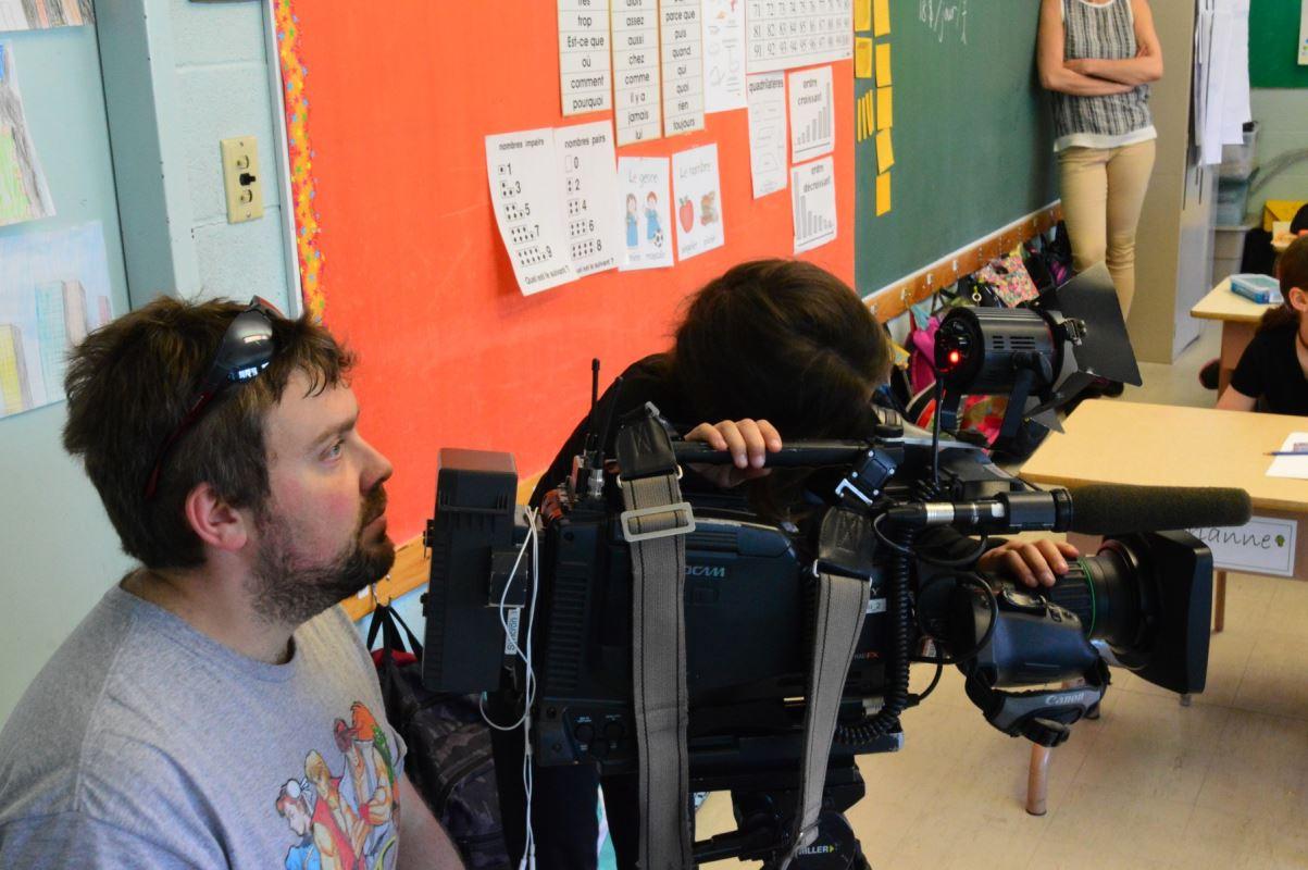 un caméraman pose un regard sur un enfant qui regarde dans la caméra