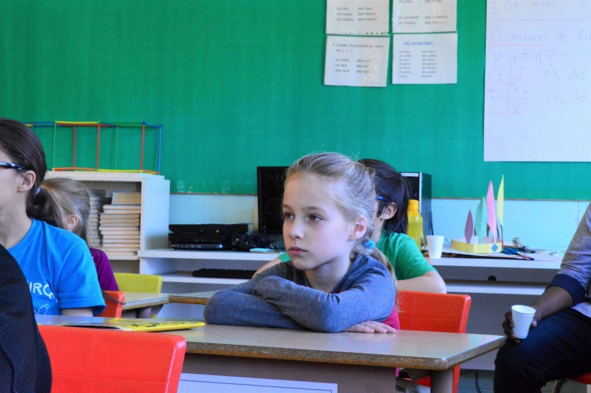 une jeune fille, bras croisés, à son bureau
