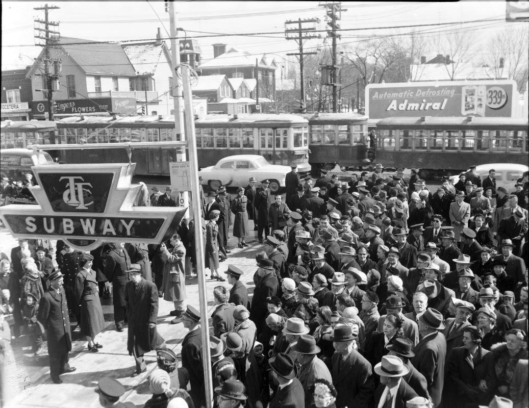 """Image d'une grande foule en attente d'entrer dans une station de métro - Panneau """"Subway"""" dans le coin inférieur gauche."""