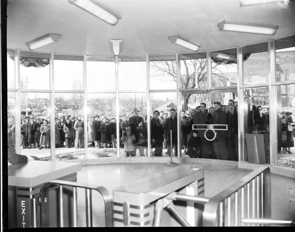 Image de personnes rassemblées devant des portes vitrées en attendant l'ouverture d'une station de la TTC