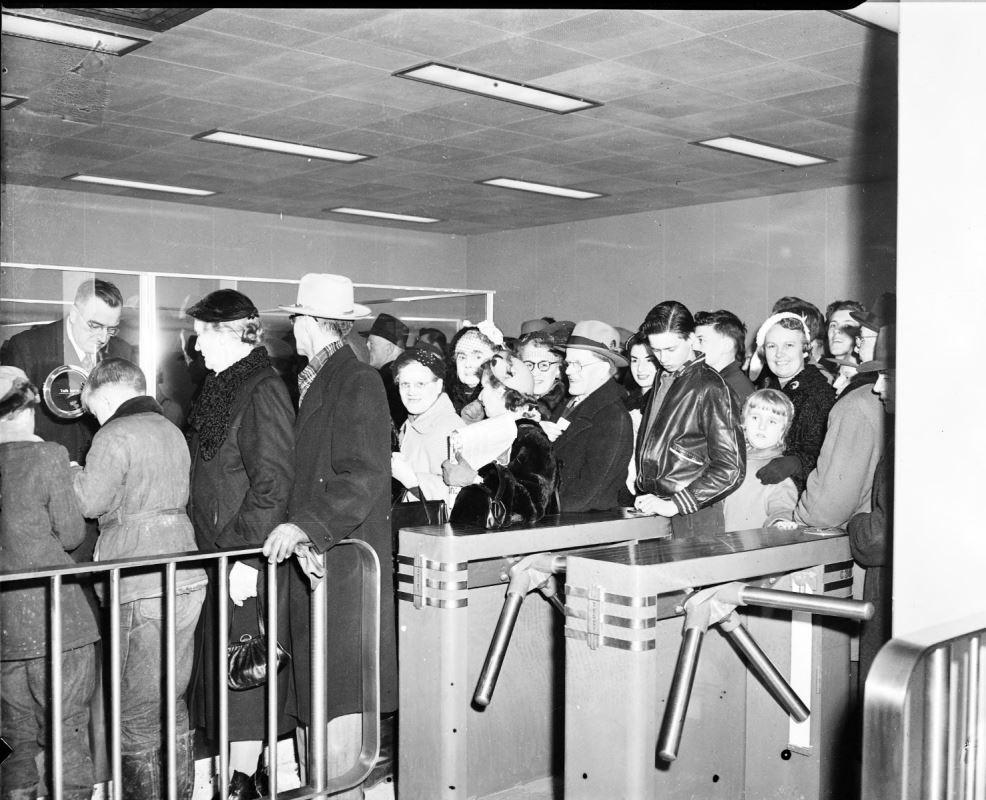 Un groupe de personnes entrant dans une station de métro via un kiosque de collecte