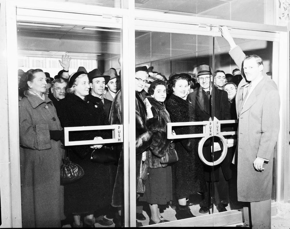 Des gens attendent à l'extérieur avec un agent de la TTC, la main sur le dessus de la porte, attendant de l'ouvrir.