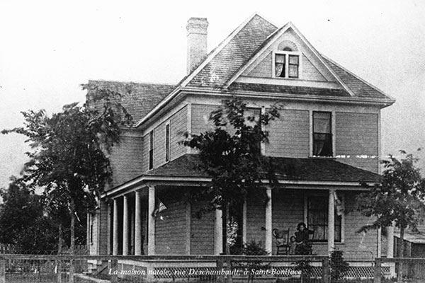 Une photo en noir et blanc d'une grande maison, au début du XXe siècle.