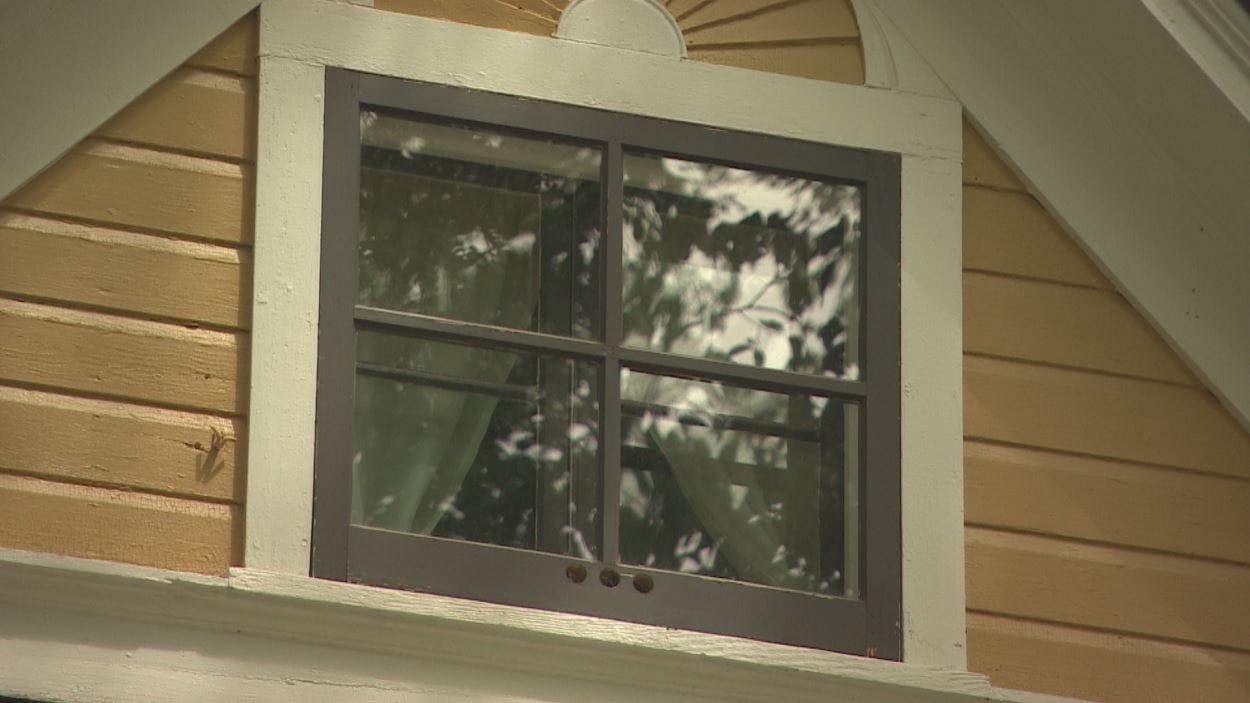 Une petite fenêtre au grenier vue de dehors.