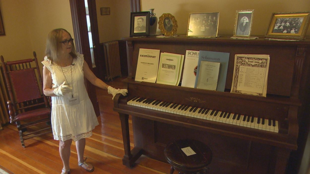 Un grand piano dans un salon et des livrets de musique.