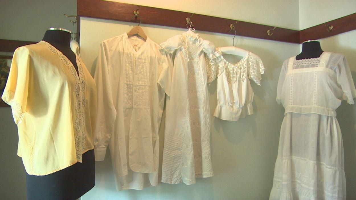 Une série de vêtements blancs accrochés au mur, dont une petite robe de baptême.