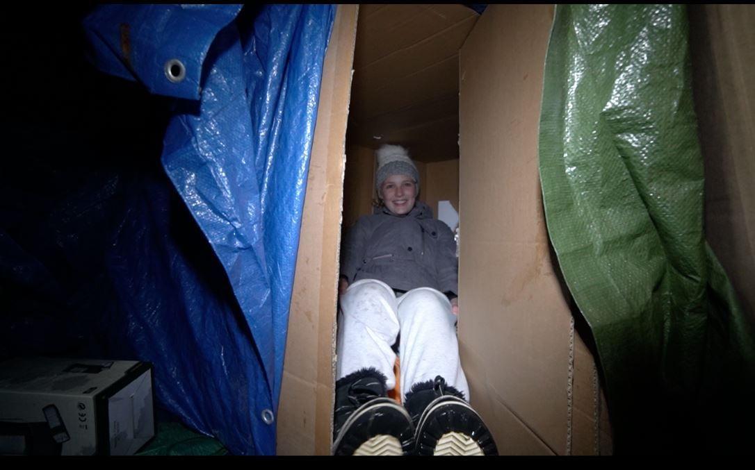 Une fille est couchée dans une boîte.