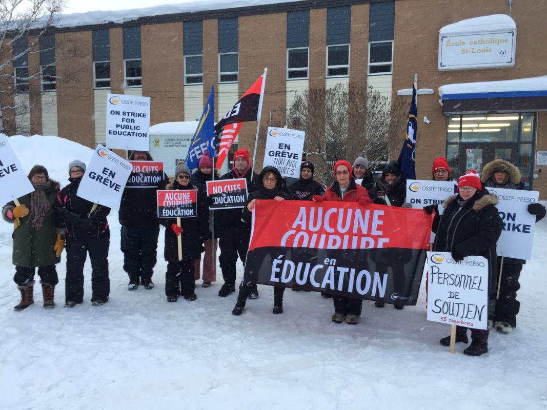 Un groupe de grèvistes tenant des pancartes posent devant une école l'hiver.