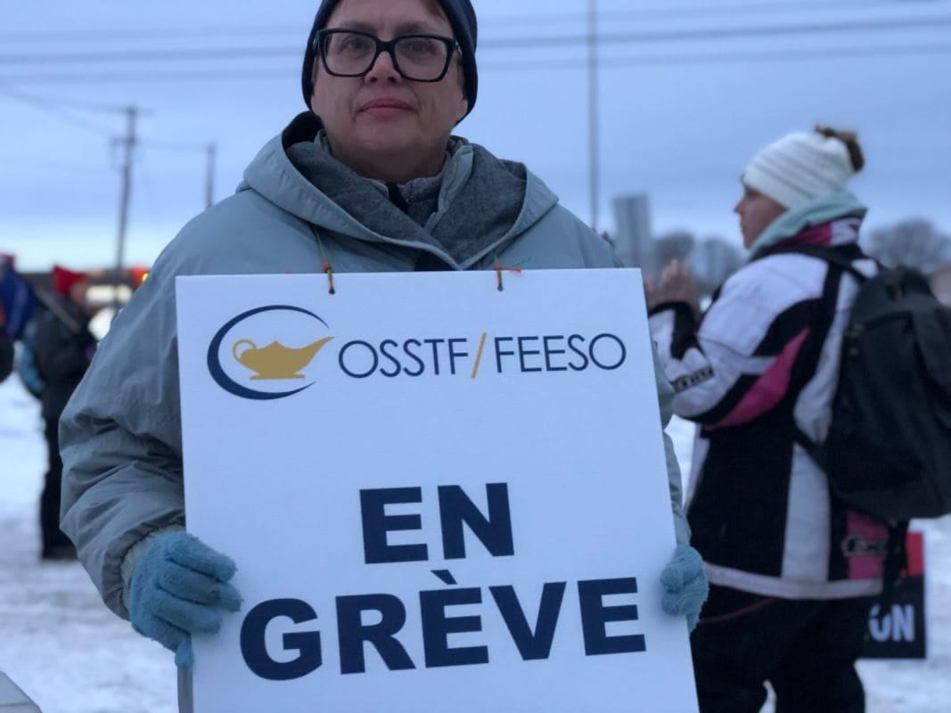 Une femme tenant une pancarte pose devant un groupe sur un piquet de grève l'hiver.