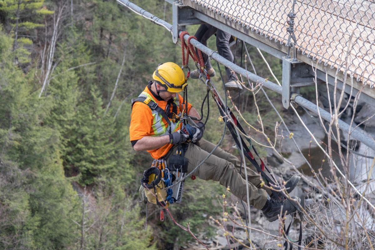 Un ingénieur est suspendu sous le pont.