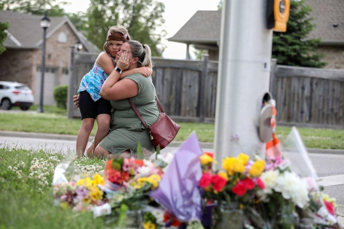 Une fillette fait une accolade à sa mère qui essuie ses larmes.